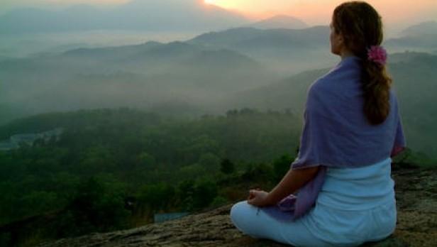 Žena meditira s pogledom u planinu