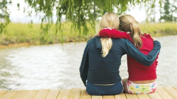 Two friends hug while sitting on the edge of a dock