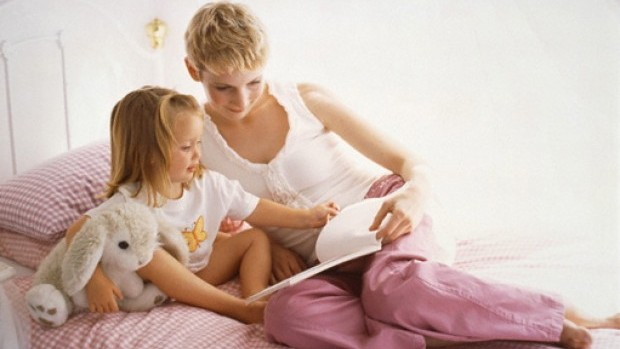 Mother and daughter reading a book --- Image by © Heide Benser/Corbis