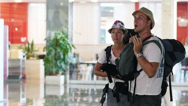 sokirani putnici gledaju u televiziju na kojoj je obavjest o otkazanom letu